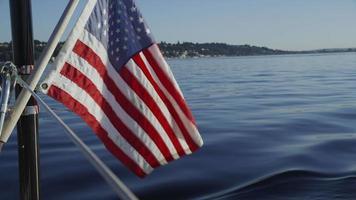 la bandiera americana ondeggia sul retro della barca a vela. girato in rosso epico per una risoluzione 4k, uhd, ultra hd di alta qualità. video
