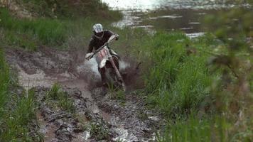 Man rides motorcycle through mud in slow motion, shot on Phantom Flex 4K video