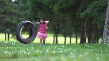 garota fantasiada de princesa de fada correndo para balançar o pneu, baleada em phantom flex 4k video