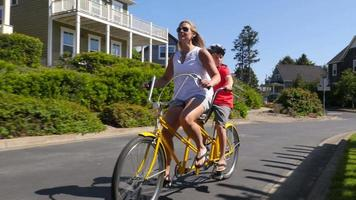 Mother and son riding tandem bicycle together in coastal vacation community video