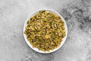 Pumpkin seeds close up. It can be used as a background photo