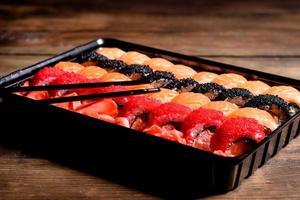 varios tipos de sushi servido sobre un fondo oscuro foto