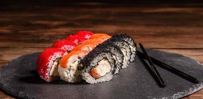 Various kinds of sushi served on a dark background photo