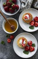 Cottage cheese pancakes, ricotta fritters on ceramic plate with  fresh strawberry. photo