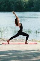 Ajuste la práctica femenina del ejercicio de yoga al aire libre foto