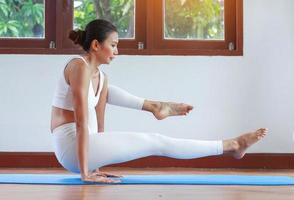 Woman doing yoga exercise at home with stretching pose concept exercise for health photo