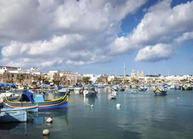maltese traditional painted luzzu boats in marsaxlokk fishing village malta photo