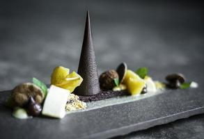 gourmet modern deconstructed chocolate cake and dried fruit dessert dish photo