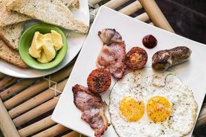 Desayuno inglés británico tradicional frito con huevos, tocino y salchichas. foto