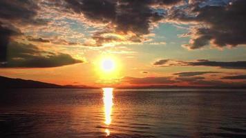 tramonto giallo densamente nuvoloso nell'acqua calma dell'oceano video
