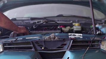 Reparador repara el motor de un coche roto en el taller de reparación de automóviles video