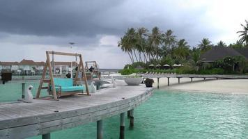 praia tropical e mar com bangalô nas maldivas video