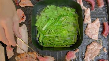 asiatisches Shabu, Grillen von Schweinefleisch, Tintenfisch und Speck auf einer rauchigen Buffetpfanne. video