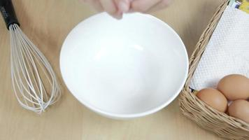 Chef breaks eggs from wooden basket into white plate and beats. video