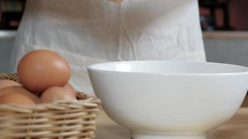 cocinera con un delantal blanco está rompiendo un huevo en la cocina de casa. video