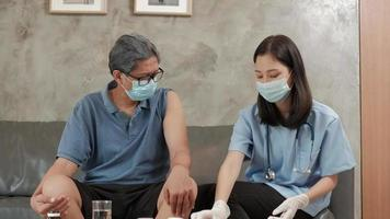 An Asian female doctor is vaccinating an elderly man at home. video