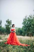 Beautiful bride in wedding dress posting in the nature photo