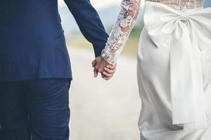 Close up of married couple holding hands in wedding day photo