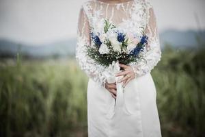 Bride hand holding flower in wedding day photo