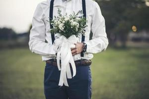 Groom hand holding flower of love in wedding day photo