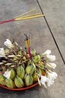 Tazón de ofrenda budista con incienso detalle de flores y frutas foto