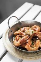 sauteed stir fry large prawns spanish tapas in metal pot photo