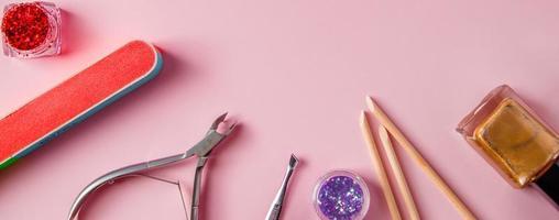 un conjunto de herramientas para manicura y cuidado de uñas sobre fondo rosa. lugar de trabajo en un salón de belleza. lugar para el texto. foto