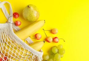 Eco-friendly cotton shopping bag. Ripe fruits in mesh bag on yellow background. Organic vegan food. Sustainable lifestyle and zero waste concept. photo