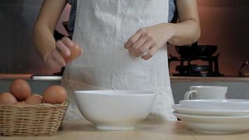 Imagens de close-up front view, uma cozinheira em um avental branco está quebrando um ovo em uma xícara para preparar uma refeição em uma mesa de madeira na cozinha da casa. comer gemas de ovo é um café da manhã saudável. video