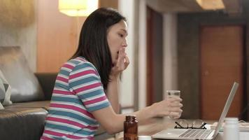 enfermedad mujer casual asiática que trabaja en casa está cansada, estresada, agotada y tiene dolor de cabeza, resfriado y gripe, tomando cápsulas de medicina, sobrecargada de trabajo al usar computadoras portátiles para hacer negocios en línea. video