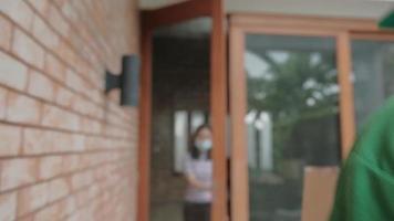 grön enhetlig leveransman med ansiktsmask ge paketpaket till asiatisk kvinnas hus. Att handla online, digitala betalningar via mobilappen är en ny normal livsstil från covid-19 karantän. video