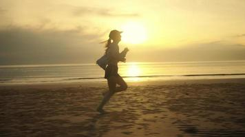 Slow-motion Side view Barefoot Woman running on the beach There are sea waves, there is a twilight light, the sun in the morning or the evening, lifestyle in vacation time. video