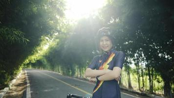Slow-motion.Asian woman smiling cutely, cyclist wearing protective helmet, crossing her arms, practicing exercise. ride in the park video