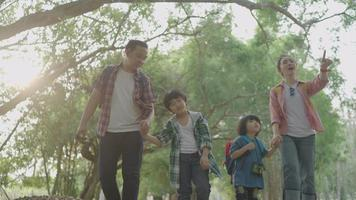 Asian father and mother teach two sons Hiking using binoculars For education Learn nature on vacation at the nature study center. video