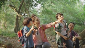 Asian parents bring two sons Hiking using binoculars For education Learn nature on vacation at the nature study center. video