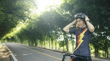 Slow-motion.Asian women A cyclist wearing a protective helmet exercise training ride a bike in the park. video