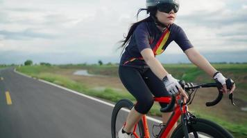 font view tracking.Asian women Orange cyclist wearing protective helmet exercise training fast riding on the roads outside the city video