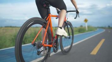 Vista posterior de seguimiento de ángulo bajo.las mujeres asiáticas ciclista naranja con casco protector entrenamiento de ejercicio conducción rápida en las carreteras fuera de la ciudad video