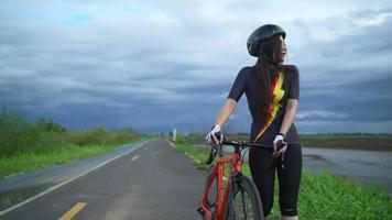 las mujeres asiáticas carro naranja ciclista con casco protector ejercicio relajarse andar en bicicleta en las carreteras fuera de la ciudad. video