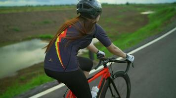 Back view tracking.Asian women Orange cyclist wearing protective helmet exercise training fast riding a bike on the roads outside the city video