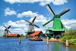 Molino de viento holandés en un campo verde cerca de Amsterdam, Países Bajos, con cielo azul y agua de río. foto