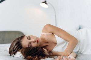 Feeling calmness. Sleepy female keeping eyes closed while dreaming about future vacation or sleeping at the bedroom. Stock photo