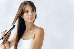 Close up retrato de mujer joven tranquila feliz disfrutando de alisarse el cabello con plancha y mirando a otro lado con una mirada de ensueño. concepto de cabello sano foto