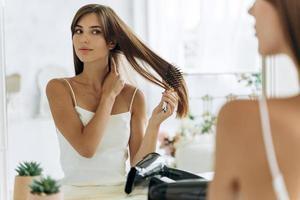 cintura para arriba retrato de la mujer reflejada en el espejo haciendo la rutina diaria mientras sostiene el cepillo para limpiar su cabello. aspecto femenino y cabello enredado. concepto de tratamiento de belleza foto