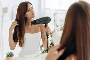 hermosa chica usando un secador de pelo y sonriendo mientras mira en el espejo. mujer sonriente secando el cabello con la máquina para secar el cabello. niña feliz mirando al espejo mientras usa secador de pelo en el baño foto