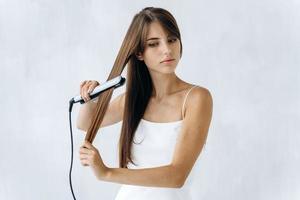 adorable joven alisándose el cabello con una plancha y mirando a un lado con emociones tranquilas. pared blanca en el fondo. concepto de cabello de mujer foto
