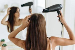 Pretty young female with a hairdryer sitting in front of the mirror and looking at her reflection while drying the hair. Care for chevelure concept photo