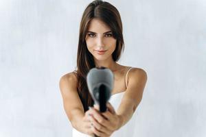 cuidado del cabello. retrato de la joven y bonita mujer posando para la cámara con un secador de pelo mientras lo sostiene como una pistola. enfocarse en las manos con un secador foto
