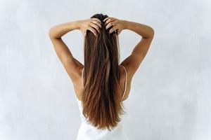 belleza y cuidado del cabello. cintura para arriba retrato de la parte posterior de la joven morena con alisar el cabello voluminoso tocándolo con las manos. aislado en blanco foto
