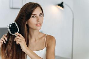 joven confiada vistiendo ropa doméstica sentada en la cama y cepillarse el pelo largo y saludable morena. mujer milenaria haciendo rutina de belleza matutina foto